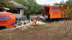 Water Damage Restoration Van And Truck With Restoration Debris Outside
